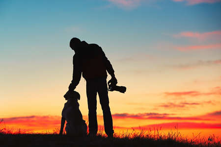 Silhouette of young photographer with his dog (labrador retriever) is enjoying sun. Photographer with mirror camera is ready to take sunrise pictures. Imagens