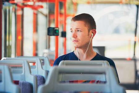 Trauriger junger Mann fährt mit der Straßenbahn (Bus). Der Alltag und das Pendeln mit öffentlichen Verkehrsmitteln zur Arbeit. Man trägt Kopfhörer und Musik hören. Standard-Bild - 60863336