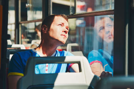 public transportation: Everyday life and commuting to work by public transportation. Handsome young man is traveling by tram (bus). Stock Photo