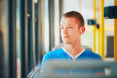public transportation: Everyday life and commuting to work by public transportation. Handsome young man is traveling by tram (streetcar). Man is wearing headphones and listening to music. Prague, Czech Republic