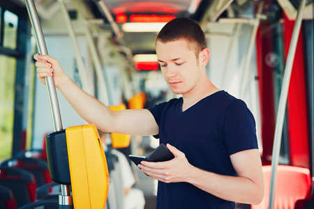 inside: Everyday life and commuting to work by bus (tram). Handsome man is paying transport ticket with mobile phone. Stock Photo
