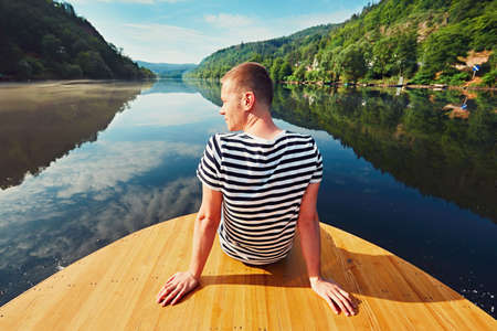 vltava river: Vacation trip on the river. Handsome man is sitting on the prow of the boat. Vltava river near Prague, Czech Republic Stock Photo