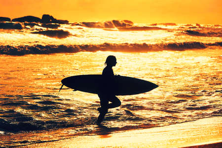 woman sunset: Silhouette of the beautiful surfer girl is enjoying vacation on the tropical beach. Young woman with surfboard at golden sunset. Sri Lanka. - back lit
