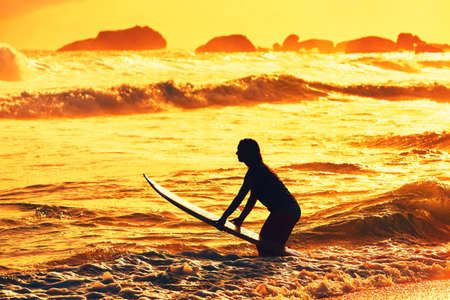 water sport: Silhouette of the beautiful surfer girl is enjoying vacation on the tropical beach. Young woman with surfboard at golden sunset. Sri Lanka. - back lit