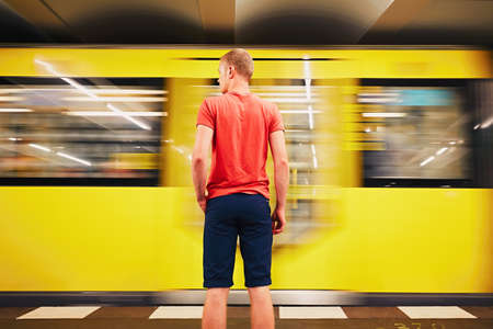 public transport: Traffic in subway. Young man is waiting for subway. Berlin, Germany