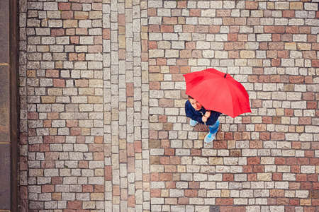 sidewalk: Rainy day. Young man is holding red umbrella and walking in rain. Street of Prague, Czech Republic. Stock Photo