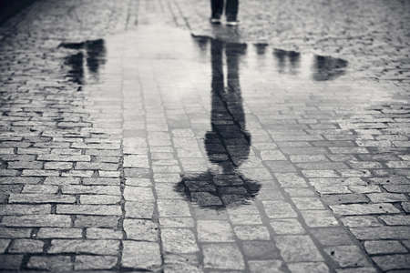 reflection: Rainy day. Reflection of young man with umbrella in puddle on the city street during rain.