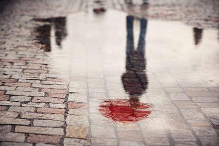 Día lluvioso. Reflexión del hombre joven con el paraguas rojo en charco en la calle de la ciudad durante la lluvia. Foto de archivo