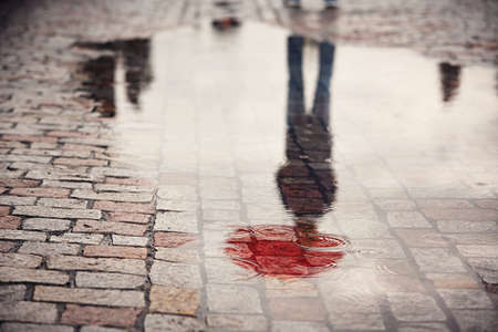 reflection: Rainy day. Reflection of young man with red umbrella in puddle on the city street during rain. Stock Photo