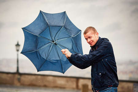 strong wind: Rain in the city. Young man is holding blue umbrella during thunderstorm. Street of Prague, Czech Republic.