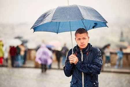 Rainy day. Young man is holding blue umbrella and walking in rain. Street of Prague, Czech Republic. Stok Fotoğraf