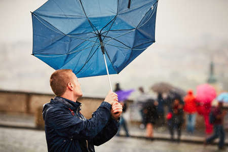 Rain in the city. Young man is holding blue umbrella during thunderstorm. Street of Prague, Czech Republic. Imagens - 60863513