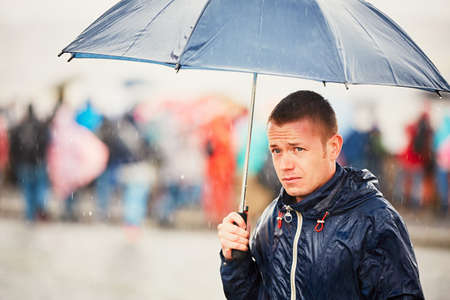 Rainy day. Young man is holding blue umbrella and walking in rain. Street of Prague, Czech Republic. Stockfoto