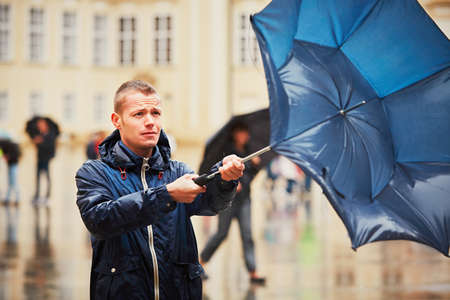 wind storm: Rain in the city. Young man is holding blue umbrella during thunderstorm. Street of Prague, Czech Republic.