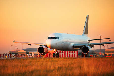 Airport at the sunset light. Airplane is taxiing to the runway for take off. Stock Photo