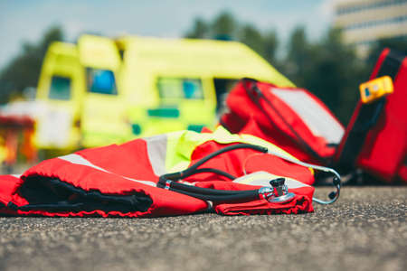 Ambulance car, stethoscope and uniform of the doctor emergency medical service - selective focus