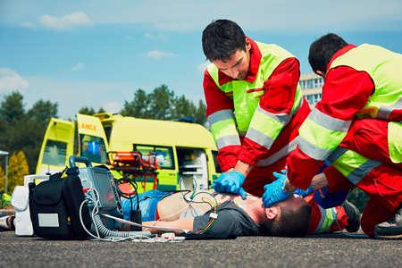 Resuscytacja krążeniowo-oddechowa. Ratownicy (lekarz i ratownik) reanimacji mężczyzna na ulicy. Zdjęcie Seryjne