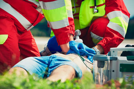 respiration: Cardiopulmonary resuscitation. Rescue team (doctor and a paramedic) resuscitating the man on the street.