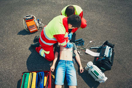 Cardiopulmonary resuscitation. Rescue team (doctor and a paramedic) resuscitating the man on the street.