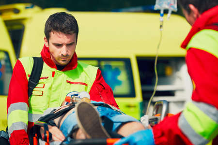 Team of rescuers (paramedic and doctor) preparing the patient after resuscitation for transport to the hospital. 스톡 콘텐츠
