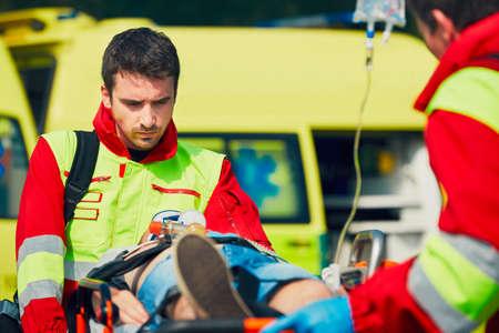 Zespół ratowników (sanitariusz i lekarz) przygotowanie chorego po reanimacji na transport do szpitala. Zdjęcie Seryjne