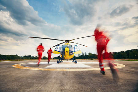 helicopter pilot: Alarm for the air rescue service. Team of rescuers (paramedic, doctor and pilot) running to the helicopter on the heliport. Stock Photo