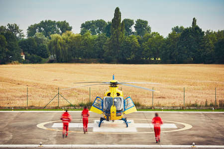 rescue: Alarm for the air rescue service. Team of rescuers (paramedic, doctor and pilot) running to the helicopter on the heliport. Stock Photo