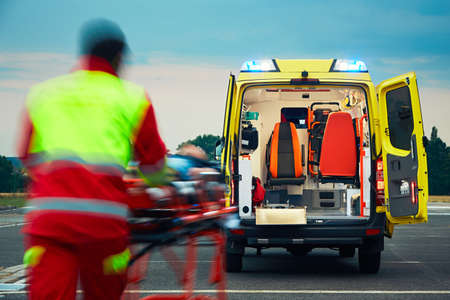 Emergency medical service. Paramedic is pulling stretcher with patient to the ambulance car. Stock Photo - 60418020