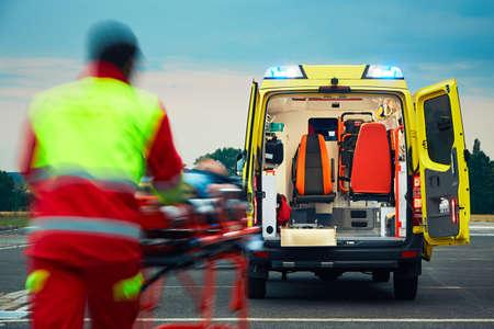 paciente en camilla: Servicio de Emergencias Médicas. El paramédico está tirando camilla con el paciente a la ambulancia.