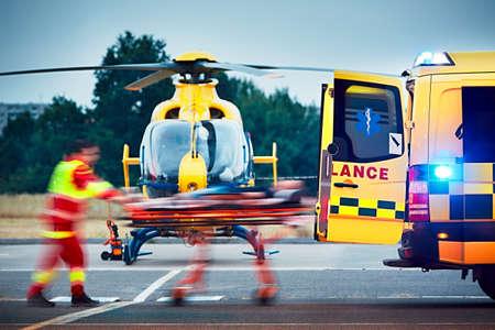 Współpraca między ratownictwa lotniczego i służby ratownictwa medycznego na ziemi. Sanitariusz ciągnie nosze z pacjentem do samochodu pogotowia.