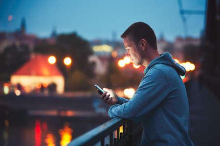 Seul dans la ville de nuit avec téléphone portable. Handsome dreamy man reading message (ou regarde la vidéo) sur son smartphone.