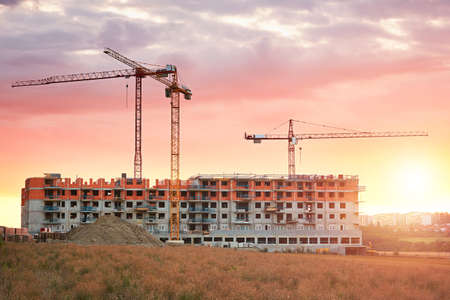 industry moody: Construction site with cranes at the amazing sunset. Construction of the new residential building. Prague, Czech Republic.
