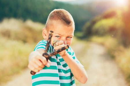 いたずら好きの少年は、石とスリング ショットを保持しています。小さな男の子は、農村風景で遊んでいます。