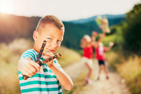 Little boy holding slingshot with stone. Boy is playing with his sisters in rural landscape. Stock Photo
