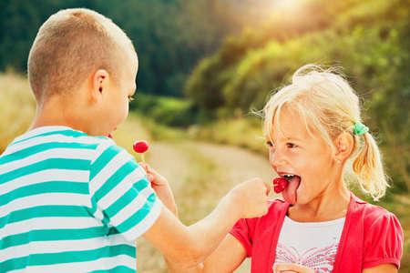 tastes: Children enjoying sunny day in holiday. Cheerful little boy and little girl tasting lollipops.