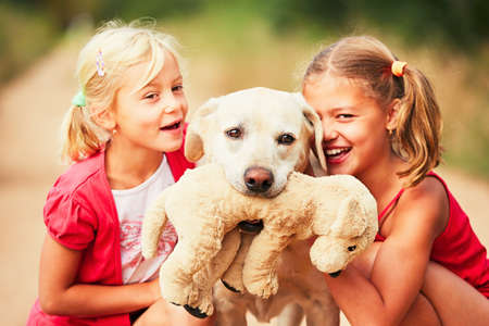 plush toy: Sisters with dog. Two girls caress yellow labrador retriever with plush toy. - selective focus on the dog