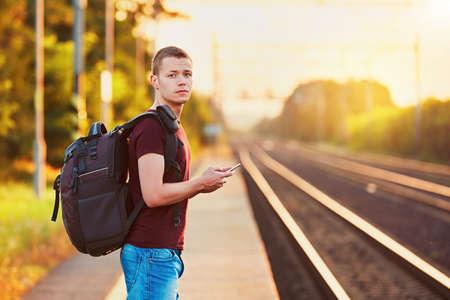 駅で旅行者が手遅れ。バックパックで若い男を逃した鉄道と待っている次の。 写真素材