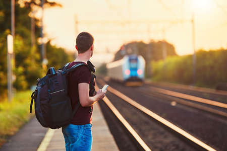 Traveler is late at the train station. Young man with backpack missed the train and waiting for next.