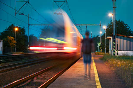 blurred motion: Traveler at the train station at the night. Young man with backpack walking on the platform. - blurred motion Stock Photo