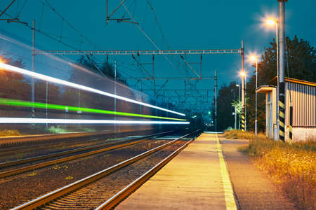 blurred motion: Railway station at the night. Passenger train on railroad tracks in blurred motion.