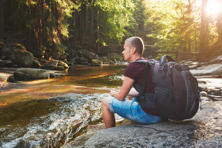 czech republic: Sunset in pure nature. Traveler with backpack resting on the riverside in forest. National park Krkonose, Czech Republic.