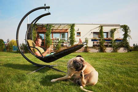 Jonge man leesboek in de schommel en grote hond rustend op de tuin van het moderne gezin huis.