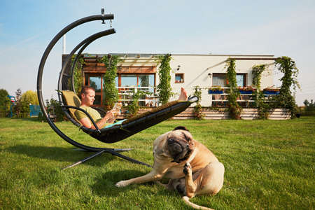 Young man reading book in the swing and large dog resting on the garden of the modern family house. Stock Photo