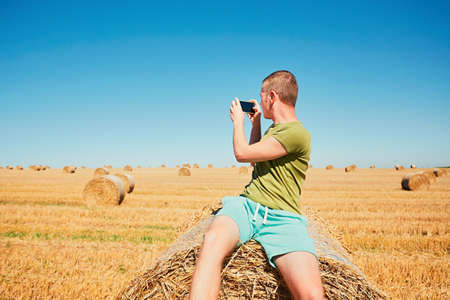 Young man taking photo by smartphone on the cornfield after harvest. Stock Photo