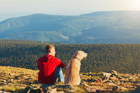 sunrise mountain: Man with dog on the trip in the mountains. Young tourist and his dog are resting and together watching the sunset.