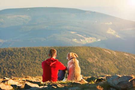 山での旅行で犬を持つ男。若い観光客と彼の犬は休憩と一緒に夕日を見てします。