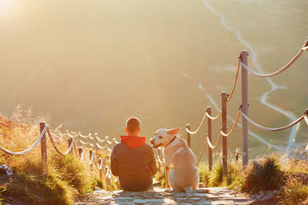Man with dog on the trip in the mountains. Young tourist and his dog are resting and together watching the sunset. -