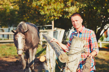man shirt: Young man and horse in countryside farm in summer day.