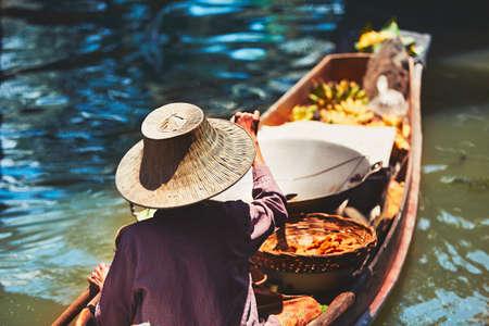 damnoen saduak: Traditional floating market Damnoen Saduak in Ratchaburi near Bangkok, Thailand. - selective focus on the old wicker hat