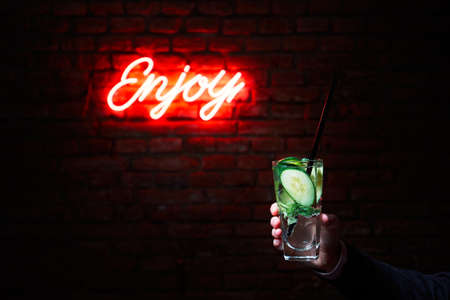gin: Hand of the young man with drink (barman or guest) in the bar in front of the brick wall with the inscription enjoy.